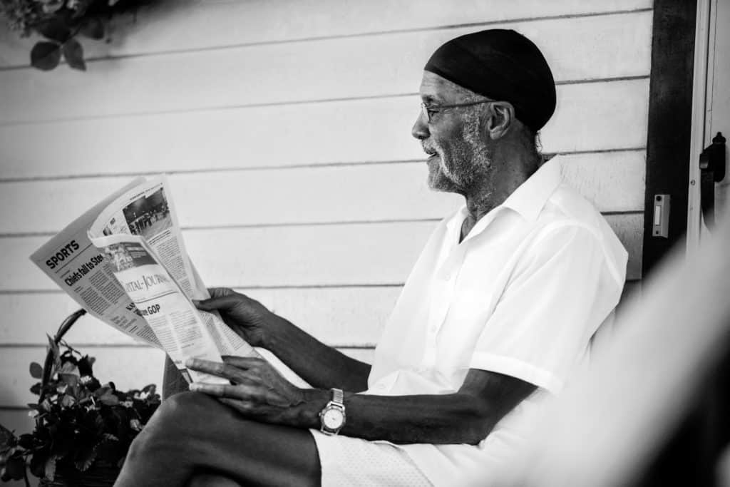 man reading a newspaper on front porch