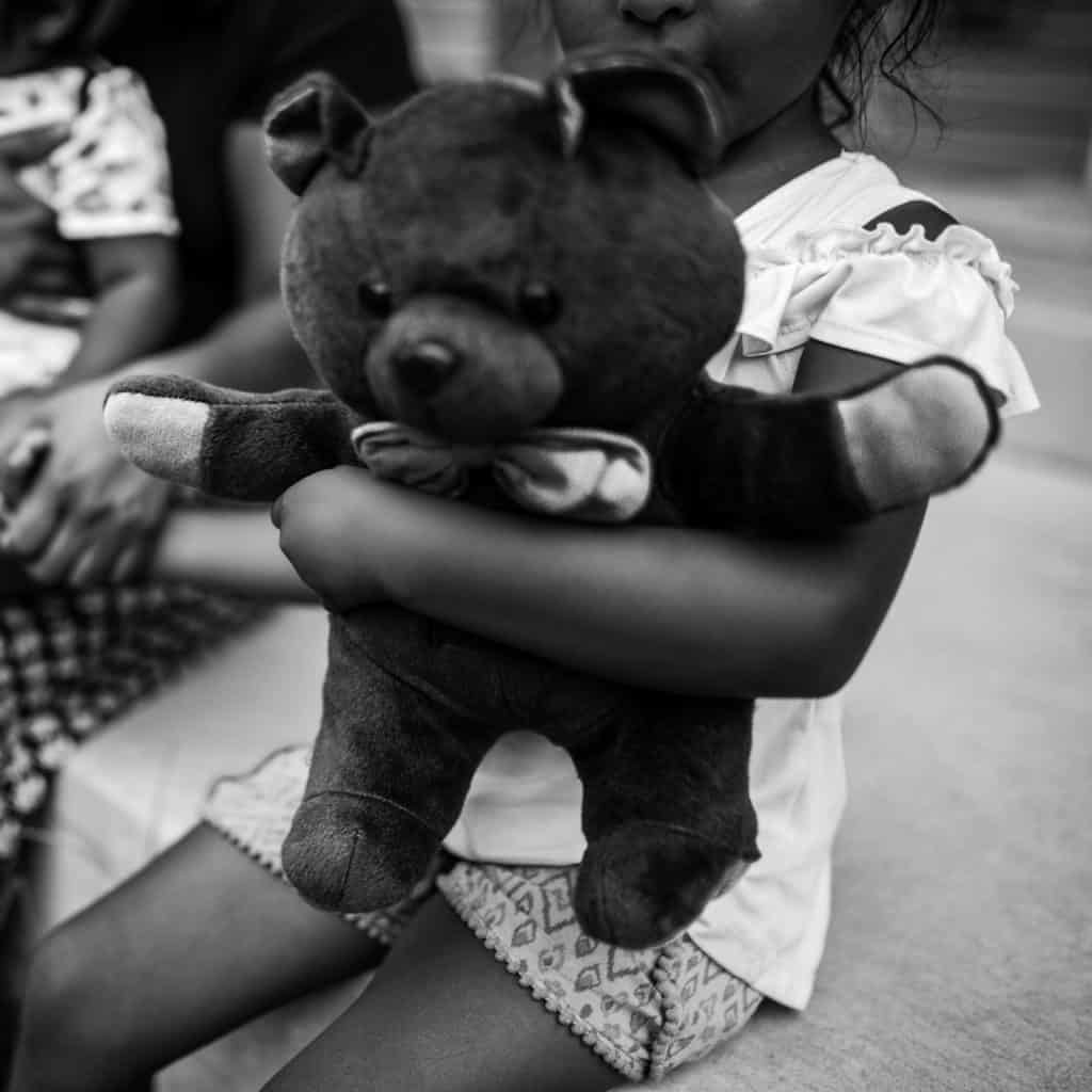 kid holding stuffed animal