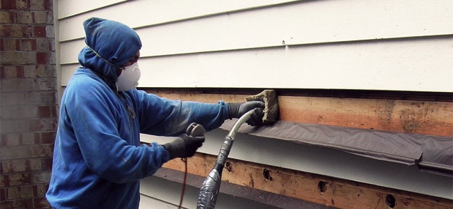 Weatherization professional adding insulation to home's exterior siding