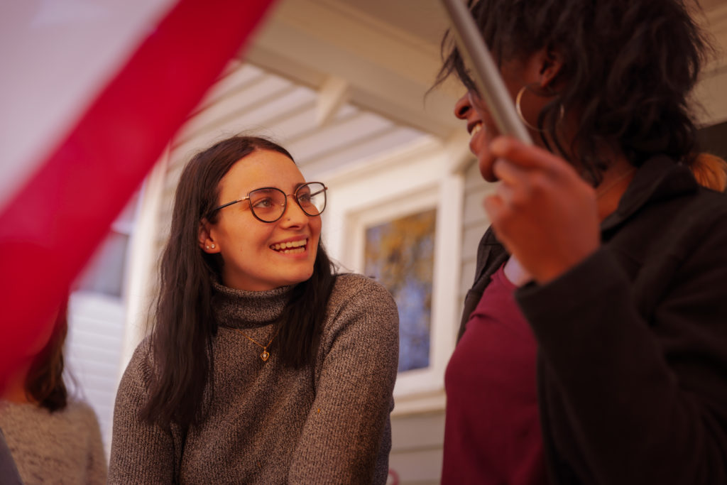 Young women smiling and talking outside house