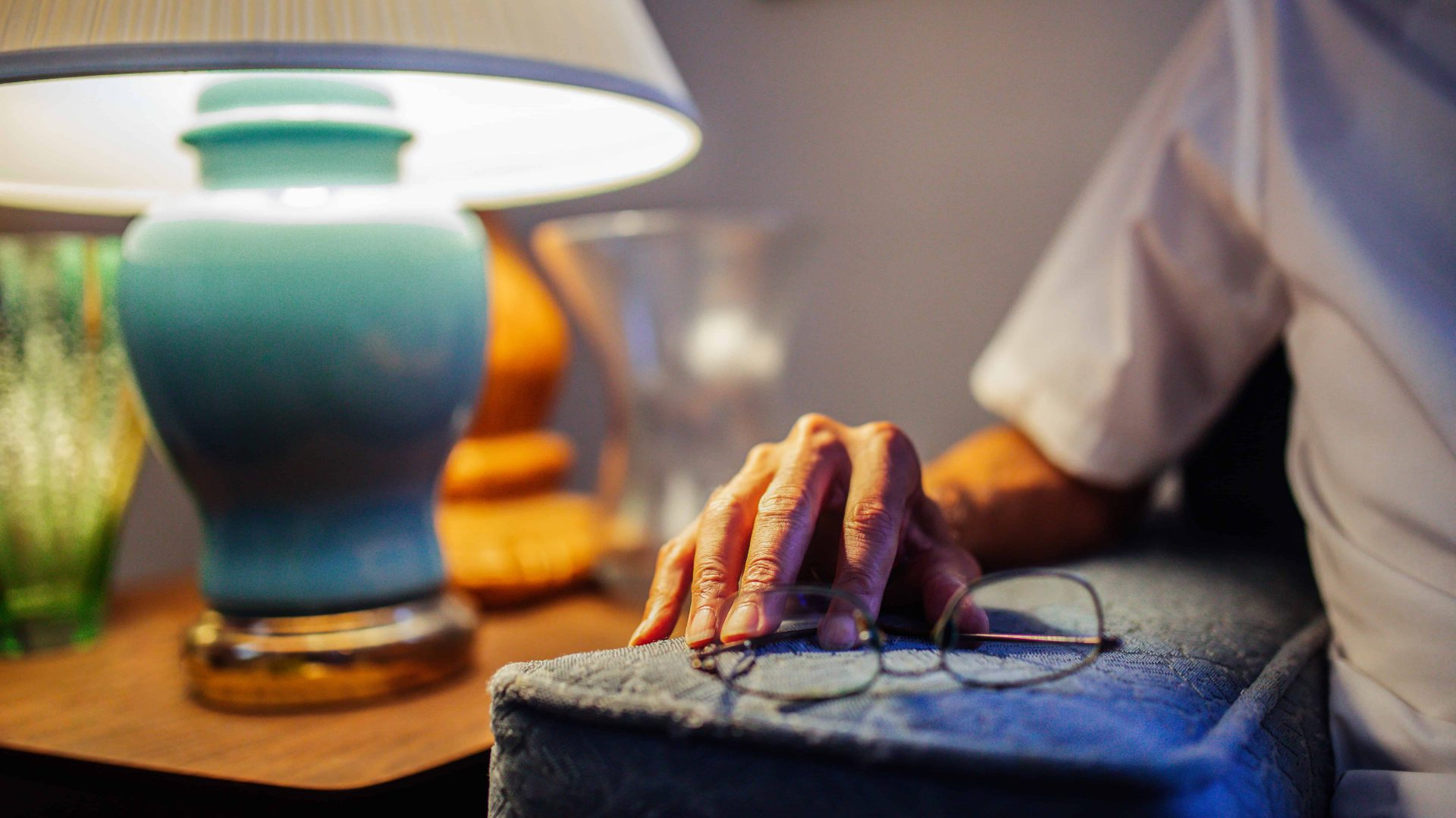 Elderly man's hand rests on the arm of his couch, next to glasses